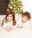Lovely children at christmas party photo of adorable kids boy and girl laying down on the sofa and laughing family home celebrate Royalty Free Stock Photography
