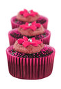 Lovely chocolate cupcakes decorated in pink on white Royalty Free Stock Image