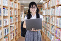 Lovely college student in library aisle Royalty Free Stock Photo