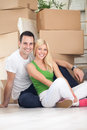 Lovely couple moving sitting on floor surrounded by boxes Stock Image