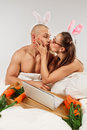 Lovely couple rabbit costumes kissing bed Stock Images