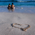 Lovely couple sitting on the beach and enjoing the sea Royalty Free Stock Photo