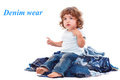 Lovely curly child sitting on the jeans pile Royalty Free Stock Photography
