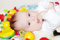 Lovely four months baby among toys lies Royalty Free Stock Photography