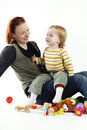 Lovely game loving mother taking care of her little daughter in photo studio baby is smiling and crying Stock Image