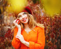 Lovely girl in beret and sweater, holding ripe apple and smiling Royalty Free Stock Photo