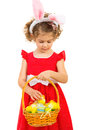 Lovely girl checking easter eggs girlw ith bunny ears in a basket isolated on white background Stock Images