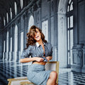 Lovely girl with striped shirt unbuttoned you can see the unde underwear black bra tying gray skirt type pencil curly hair Royalty Free Stock Image