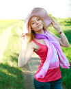 Lovely girl in a summer hat on a green glade posing Stock Image