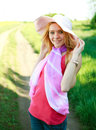 Lovely girl in a summer hat on a green glade posing Royalty Free Stock Photo