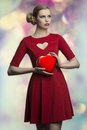 Lovely girl with valentine gift portrait of romantic blonde woman creative hair style and red sexy dress taking in the hands one Royalty Free Stock Image