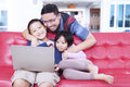 Lovely kids with dad using laptop on sofa two happy little girl sitting while to enjoy movie their at home Stock Photos