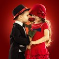 Lovely little boy giving a rose to girl fashionable and her excited love concept Royalty Free Stock Image
