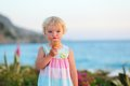 Lovely little girl eating ice cream on the beach happy healthy child cute blonde toddler enjoying summer vacations delicious Royalty Free Stock Photo