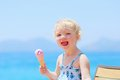 Lovely little girl eating ice cream on the beach happy healthy child cute blonde toddler enjoying summer vacations delicious Royalty Free Stock Photography