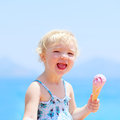 Lovely little girl eating ice cream on the beach happy healthy child cute blonde toddler enjoying summer vacations delicious Royalty Free Stock Image
