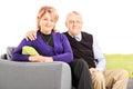 Lovely mature couple sitting on sofa isolated white background Royalty Free Stock Photo