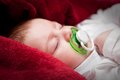 Lovely months baby sleeping on bed covered with red blanket soft Stock Photo