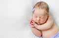 Lovely newborn girl sleeping with hands under head top view violet flower and panties Stock Photo