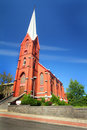 Lovely old brick church an intricately detailed with a tall white steeple under clear blue skies Stock Photos