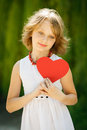 Lovely pensive girl holding heart shape outdoors Stock Photos
