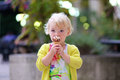 Lovely preschooler girl eating ice cream outdoors happy little child adorable blonde toddler in beautiful dress walking on crowded Royalty Free Stock Images