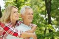 Lovely senior couple portrait of hiking in the forest elderly women embracing her men while standing outdoors and spending time Stock Photography