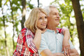 Lovely senior couple portrait of hiking in the forest elderly women embracing her men while standing outdoors and spending time Royalty Free Stock Photos