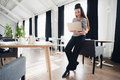 Lovely shapely woman in business suit standing near table with laptop. Stands close to chairs are pushed under table.