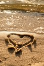 Lovely small heart sketched in salt  sand at beach. Evening warm colors of sunset mirror in water level. Royalty Free Stock Photo