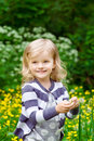 Lovely smiling little girl with blade of grass in her hands in summer day vertical portrait a Royalty Free Stock Photo
