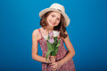 Lovely smiling little girl in hat with bouquet of flowers Royalty Free Stock Photo