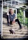 Lovely smiling rocker girl and little black kitten on ladder Royalty Free Stock Photo