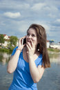 Lovely teen girl with enthusiasm talking on the phone and receiving joyful news and surprise. Royalty Free Stock Photo