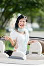 Lovely teenager stands in the cabriolet car with put off sunglasses Royalty Free Stock Photo