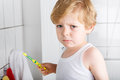 Lovely toddler with blue eyes and blond hair brushing his teeth boy is sad about at home Royalty Free Stock Photo