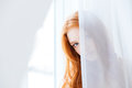 Lovely woman hiding behind white curtains Royalty Free Stock Photo