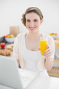 Lovely woman sitting in front of her laptop in her kitchen while holding a glass of orange juice smiling at camera Stock Image