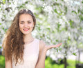 Lovely young curly girl with a charming smile shows hand gesture in the blooming garden Stock Images
