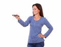 Lovely young female pointing remote control Royalty Free Stock Photo