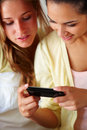 Lovely young friends looking at mobile together Royalty Free Stock Photo