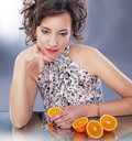 Lovely young girl with fresh halves of oranges sit Royalty Free Stock Images