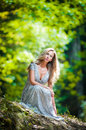 Lovely young lady wearing elegant white dress enjoying the beams of celestial light on her face in enchanted woods pretty blonde Royalty Free Stock Photo