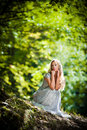 Lovely young lady wearing elegant white dress enjoying the beams of celestial light on her face in enchanted woods pretty blonde Stock Images