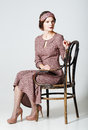 Lovely young woman sitting on chair portrait in retro style a Stock Image