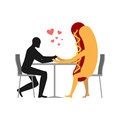 Lover in coffee room. Man and hot dog is sitting at a table.