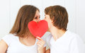 Lover couple kissing with a red heart in bed Royalty Free Stock Photo