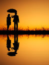 In lover reflection of man and woman holding umbrella in evening sunset silhouette women Stock Photo