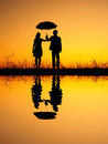 In lover reflection of man and woman holding umbrella in evening sunset silhouette women Stock Photography