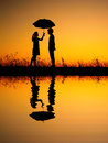 In lover reflection of man and woman holding umbrella in evening sunset silhouette women Royalty Free Stock Photos
